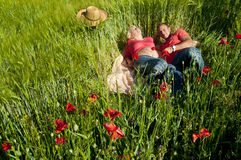 Portrait of a pregnant couple lying on blanket in a wheat field Royalty Free Stock Photo