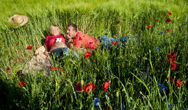 Portrait of a pregnant couple lying on blanket in a wheat field Stock Image