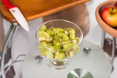Portrait of pregnant mother cuts kiwi fruit Royalty Free Stock Image