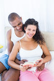 Portrait of pregnant wife holding book with husband on bed Royalty Free Stock Photography