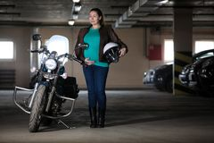 Portrait of pregnant woman biker standing next to motorcycle with white helmet in hand, underground garage. Portrait of pregnant woman biker standing next to royalty free stock photos