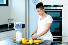 Portrait of pregnant woman cutting fruits on chopping board Royalty Free Stock Image