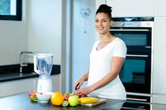 Portrait of pregnant woman cutting fruits on chopping board Royalty Free Stock Photography