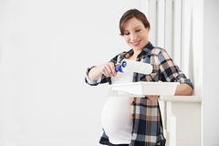 Portrait Of Pregnant Woman Decorating Nursery Stock Images