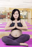 Pregnant woman meditating in the fitness center. Portrait of pregnant woman doing a workout while meditating in the fitness center stock photo