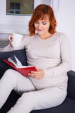 Portrait of pregnant woman drinking tea and reading book at home Stock Photos