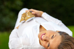 Portrait pregnant woman lying on the grass. Portrait of a beautiful pregnant woman lying on the grass with a baby shoes on her belly Royalty Free Stock Image