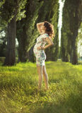 Portrait of the pregnant woman in the park Stock Photos