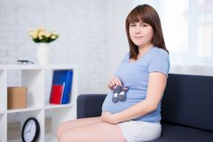 Portrait of pregnant woman posing with little socks Royalty Free Stock Photography
