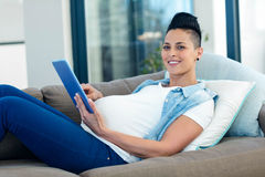 Portrait of pregnant woman relaxing on sofa with her digital tablet Stock Images