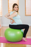 Portrait of pregnant woman sitting on exercise ball Stock Photos