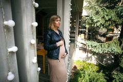 Portrait of a pregnant woman in the street. Beautiful blonde girl touching her belly, Summer street shot royalty free stock photography