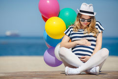 Portrait of pregnant woman with sunglasses and hat Stock Photo