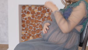 Portrait of pregnant woman by window caressing her belly stock video footage