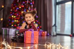 Portrait of a preschool child girl laying down. Studio shot. Little black girl oppening gift box, wearing beautiful dress, studio shot, christmas, child, kid royalty free stock photos
