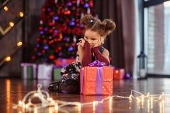 Portrait of a preschool child girl laying down. Studio shot. Little black girl oppening gift box, wearing beautiful dress, studio shot, christmas, child, kid royalty free stock photography