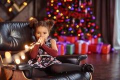 Portrait of a preschool child girl laying down. Studio shot. Little black girl oppening gift box, wearing beautiful dress, studio shot, christmas, child, kid stock photos
