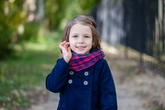 Portrait of preschooler girl in the autumn park. Young toddler girl walking outdoor Stock Photos