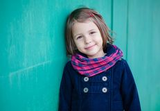 Portrait of preschooler girl near green wall. Young toddler girl outdoor. This image has attached release Stock Photography