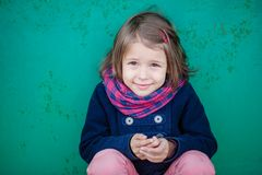 Portrait of preschooler girl sitting near wall. Young toddler girl outdoor. This image has attached release Stock Photos