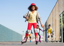 African girl rollerblading with friends at stadium. Portrait of preteen African girl in helmet rollerblading with her friends at stadium outdoors Stock Photography
