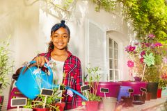 Beautiful African girl watering potted flowers royalty free stock photo
