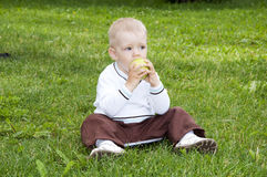 Portrait of a preteen boy with a apple. In his hand and green grass in the background Stock Photo