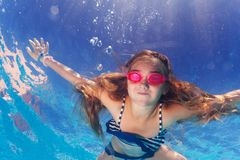 Girl in goggles learning holding breath underwater Stock Image