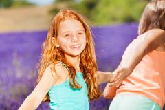 Happy girl walking with friend in lavender field. Portrait of preteen red-headed girl holding hand of her friend while walking in lavender field Royalty Free Stock Photos