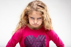 Preteen sulky girl making angry face. Portrait of preteen sulky girl making angry face against plain background Royalty Free Stock Images