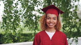 Portrait of pretty African American girl graduating student in red gown and mortarboard standing outdoors, smiling and
