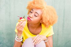 Colorful portrait of an african woman with sweet dessert. Portrait of a pretty african woman in yellow t-shirt holding a sweet dessert with cherry on the green Royalty Free Stock Photos