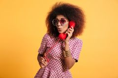 Portrait of a pretty afro american woman. In retro style clothes talking on telephone isolated over yellow background Royalty Free Stock Photos
