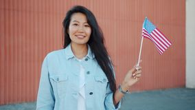 Portrait of pretty Asian girl holding US flag outdoors smiling looking at camera. Portrait of pretty Asian girl holding official US flag outdoors smiling looking stock video footage