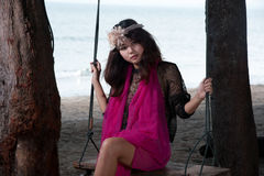 Portrait of pretty Asian woman sitting on a swing . Royalty Free Stock Photos