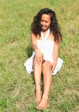 Portrait of sitting pretty girl. Portrait of pretty barefoot Papuan girl in white dress - smiling young Indonesian woman sitting in grass Royalty Free Stock Images