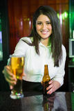 Portrait of pretty bartender serving beer at bar counter Stock Image