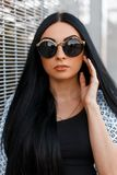 Portrait of a pretty beautiful hipster young woman in trendy sunglasses with luxurious long hair in stylish summer clothes royalty free stock photography