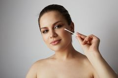 Portrait pretty beauty girl refreshing skin face with white cotton buds over gray studio background.Model with light. Nude make-up.Healthcare skin makeup royalty free stock photos