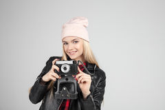 Portrait of pretty blond hair smileing young teenage hipster woman model with retro photo camera wearing a pink hat Stock Photo