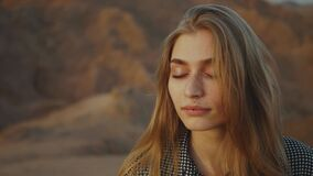 Portrait of pretty blond woman with closed eyes on sunset. Happy young woman standing in a desert mountains, sunset