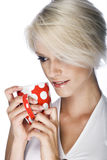 Portrait of a pretty blond woman daydreaming. Portrait of a pretty blond woman with short hair daydreaming while holding a red mug royalty free stock photo