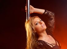 Portrait of a pretty blond woman pole dancing Royalty Free Stock Photography