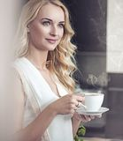 Portrait of a pretty blonde drinking a cup of coffee Royalty Free Stock Photos