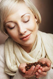 Portrait of pretty blonde girl hold coffee beans in hands Royalty Free Stock Images