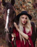 Portrait of a pretty blonde girl holding a brown horse, taking care of it royalty free stock images