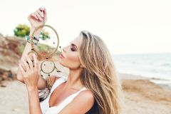 Portrait of pretty blonde girl with long hair on beach. She wears white dress, holds ornamentation in hand and keeps. Portrait of pretty blonde girl with long royalty free stock images