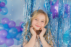 Portrait of Pretty blonde little girl with color balloons. In a decorated studio Royalty Free Stock Photo