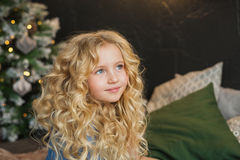 Portrait of pretty blonde little girl smiles and looks side on a bed in Christmas time Stock Images