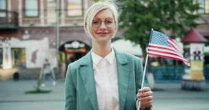 Portrait of pretty blonde standing outdoors with American flag smiling. Portrait of pretty young blonde standing outdoors with American flag smiling looking at stock video footage